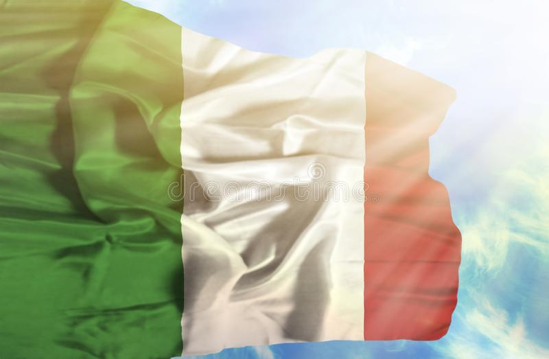 Drapeau de ondulation de l'Italie contre le ciel bleu avec des rayons de soleil image libre de droits