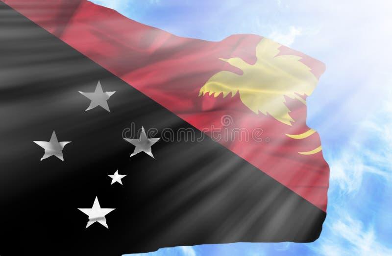 Drapeau de ondulation de la Papouasie-Nouvelle-Guin?e contre le ciel bleu avec des rayons de soleil photos libres de droits