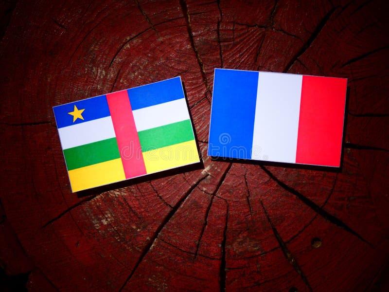 Drapeau de République Centrafricaine avec le drapeau français sur un tronçon d'arbre i photo stock