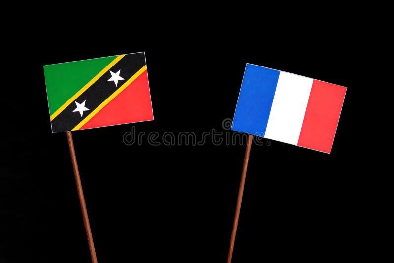 Drapeau de saint Kitts et du Niévès avec le drapeau français sur le noir image stock