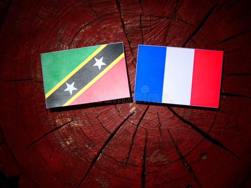 Drapeau de saint Kitts et du Niévès avec le drapeau français sur un isolant de tronçon d'arbre image libre de droits