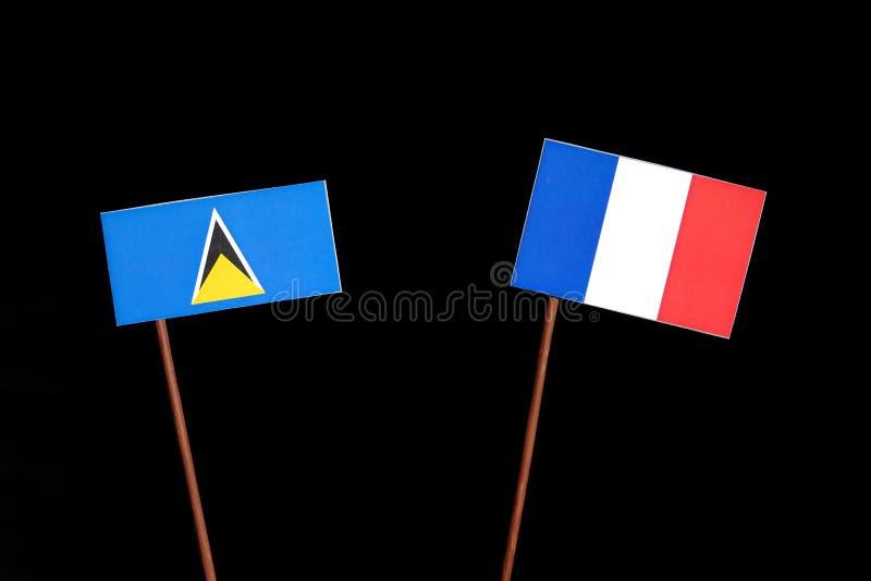 Drapeau de Sainte-Lucie avec le drapeau français sur le noir images stock