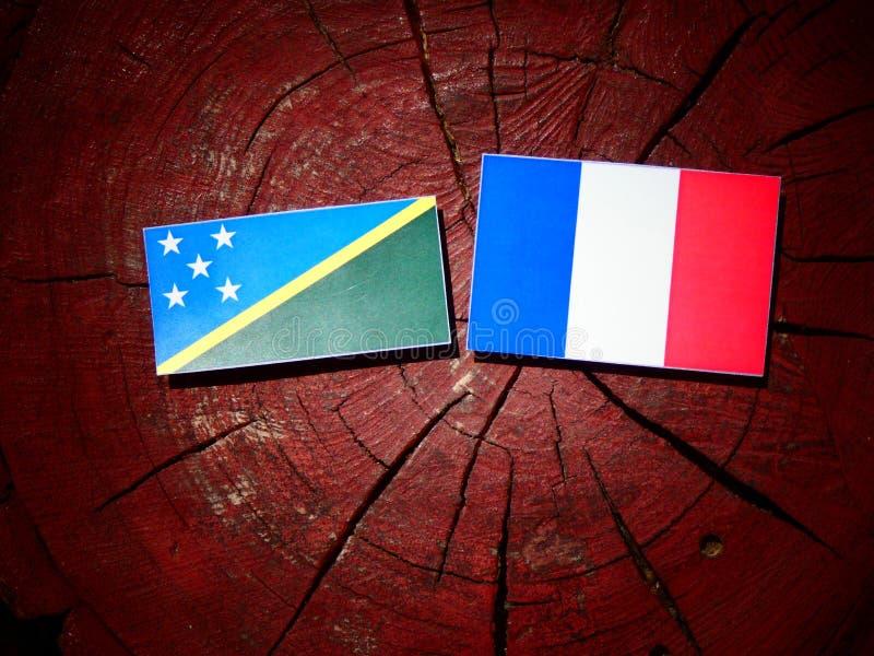 Drapeau de Solomon Islands avec le drapeau français sur un tronçon d'arbre d'isolement image stock