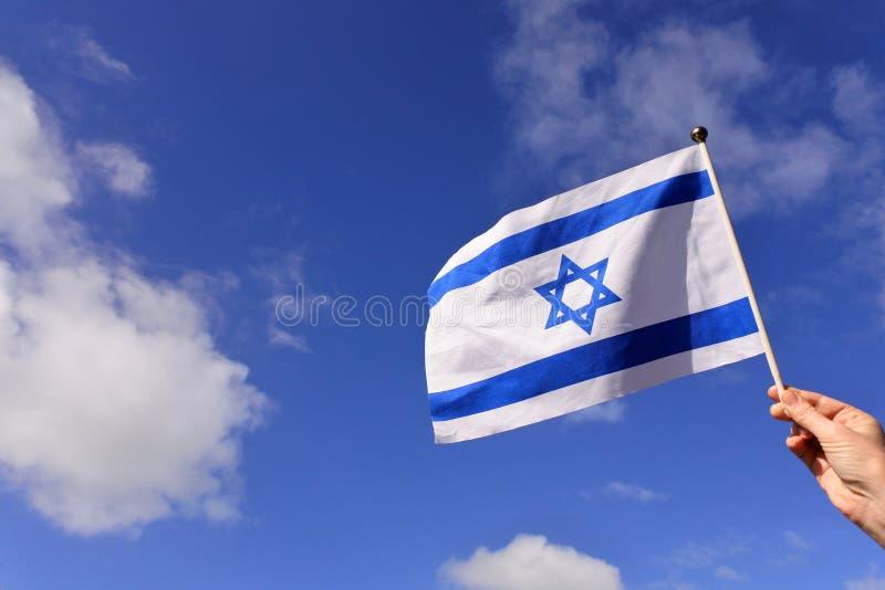 Drapeau de vague de femme de l'Israël contre le ciel bleu photo libre de droits