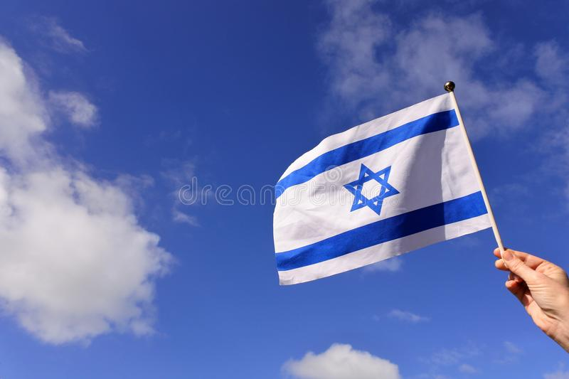 Drapeau de vague de femme de l'Israël contre le ciel bleu photo libre de droits