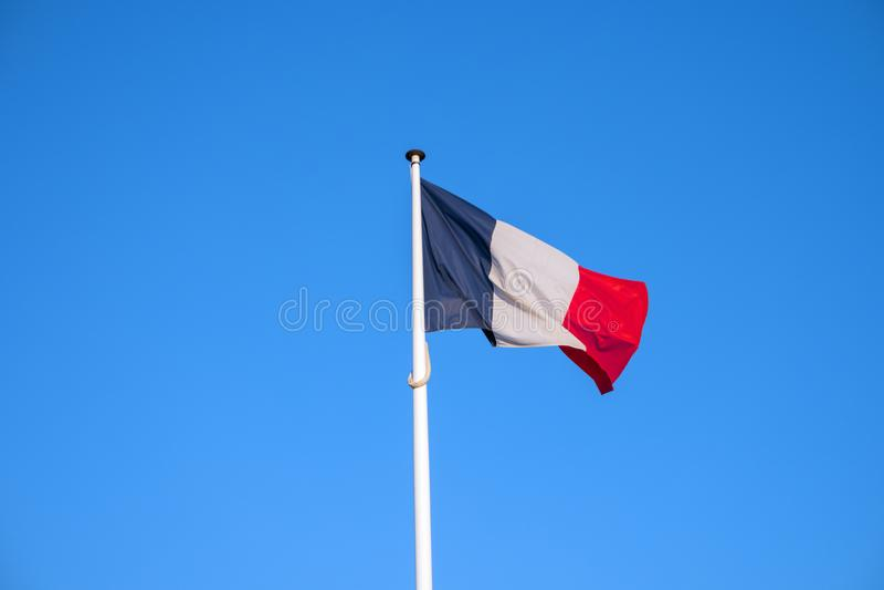 Drapeau des Frances ondulant en vent, fond de ciel bleu photo libre de droits