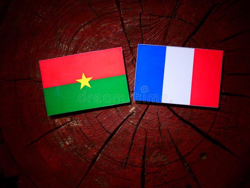 Drapeau du Burkina Faso avec le drapeau français sur un tronçon d'arbre d'isolement images libres de droits