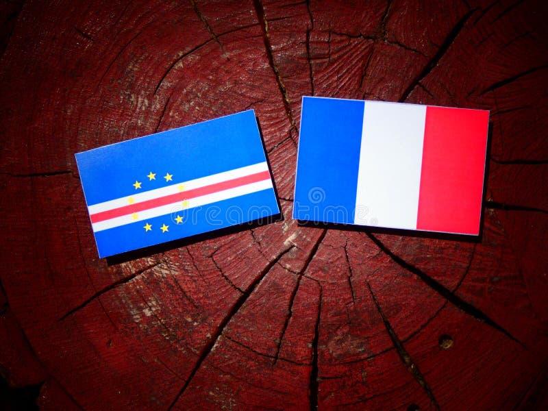 Drapeau du Cap Vert avec le drapeau français sur un tronçon d'arbre d'isolement photographie stock libre de droits