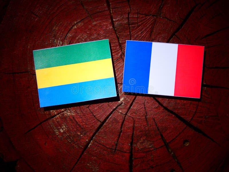Drapeau du Gabon avec le drapeau français sur un tronçon d'arbre d'isolement photos stock