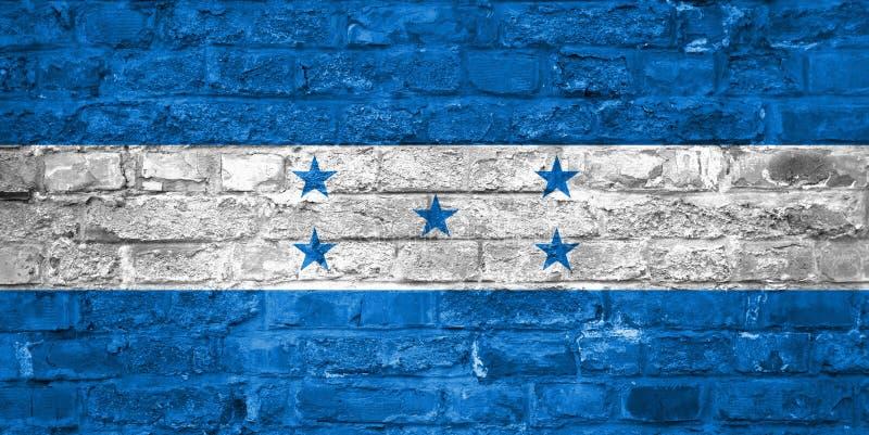 Drapeau du Honduras au-dessus d'un vieux fond de mur de briques, surface photo stock