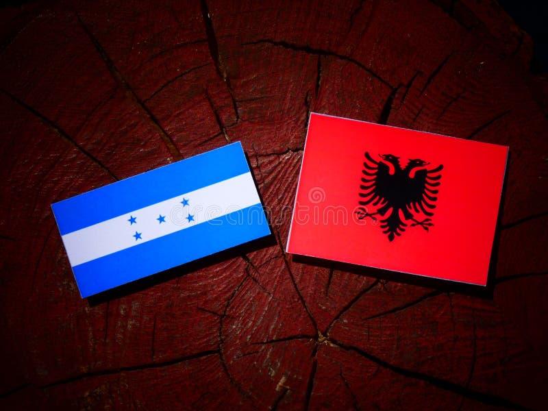 Drapeau du Honduras avec le drapeau albanais sur un tronçon d'arbre d'isolement illustration stock