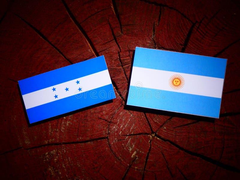Drapeau du Honduras avec le drapeau argentin sur un tronçon d'arbre d'isolement illustration libre de droits