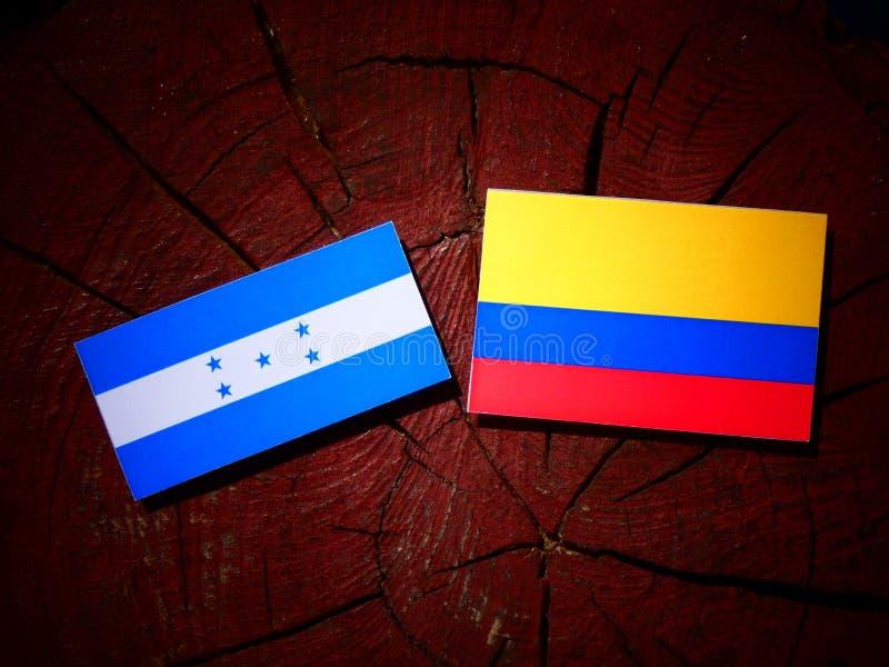 Drapeau du Honduras avec le drapeau colombien sur un tronçon d'arbre d'isolement illustration stock