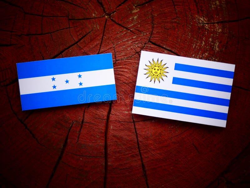 Drapeau du Honduras avec le drapeau d'Uruguaian sur un tronçon d'arbre d'isolement illustration libre de droits