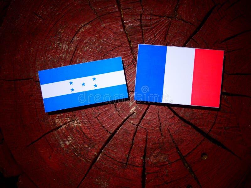 Drapeau du Honduras avec le drapeau français sur un tronçon d'arbre d'isolement photo libre de droits