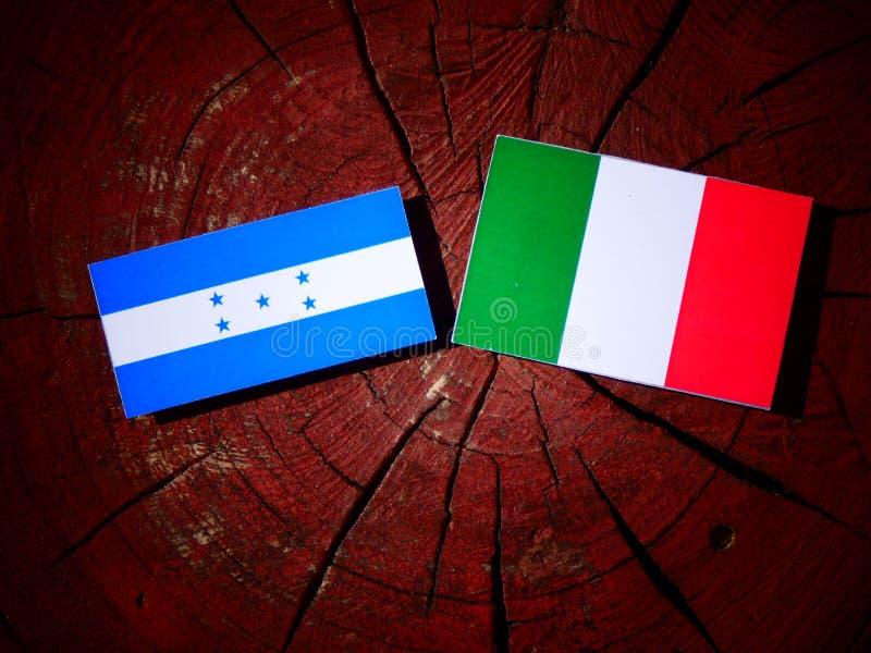 Drapeau du Honduras avec le drapeau italien sur un tronçon d'arbre d'isolement illustration de vecteur