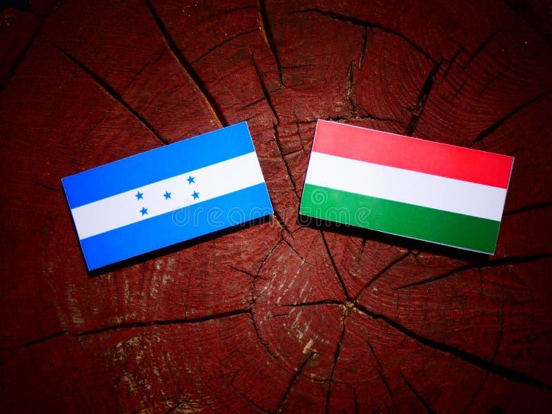 Drapeau du Honduras avec le drapeau hongrois sur un tronçon d'arbre d'isolement illustration de vecteur