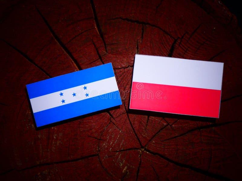 Drapeau du Honduras avec le drapeau polonais sur un tronçon d'arbre d'isolement illustration de vecteur