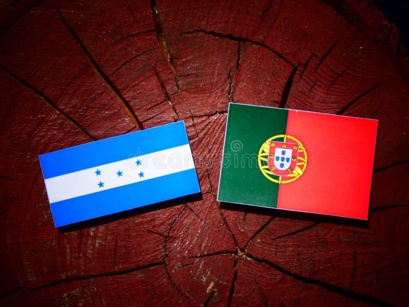 Drapeau du Honduras avec le drapeau portugais sur un tronçon d'arbre d'isolement illustration stock