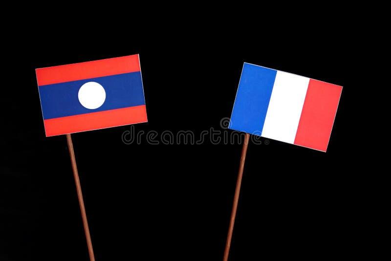 Drapeau du Laos avec le drapeau français d'isolement sur le noir photo stock