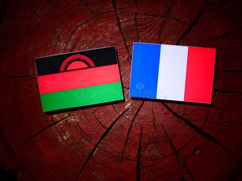 Drapeau du Malawi avec le drapeau français sur un tronçon d'arbre d'isolement images stock