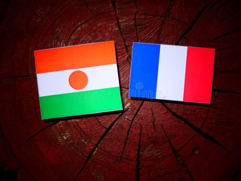 Drapeau du Niger avec le drapeau français sur un tronçon d'arbre d'isolement photos libres de droits