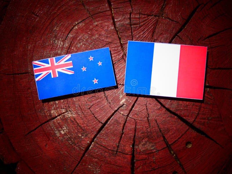 Drapeau du Nouvelle-Zélande avec le drapeau français sur un tronçon d'arbre d'isolement image stock