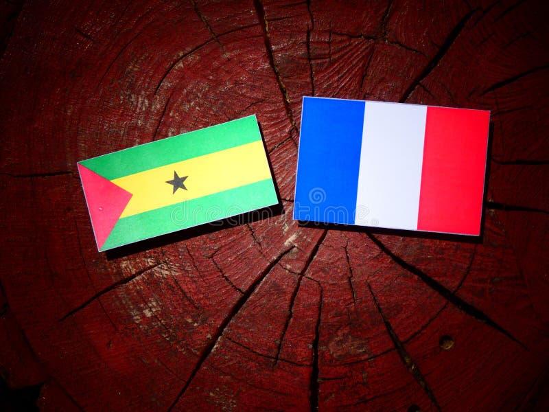 Drapeau du Sao-Tomé-et-Principe avec le drapeau français sur un isolant de tronçon d'arbre photos stock