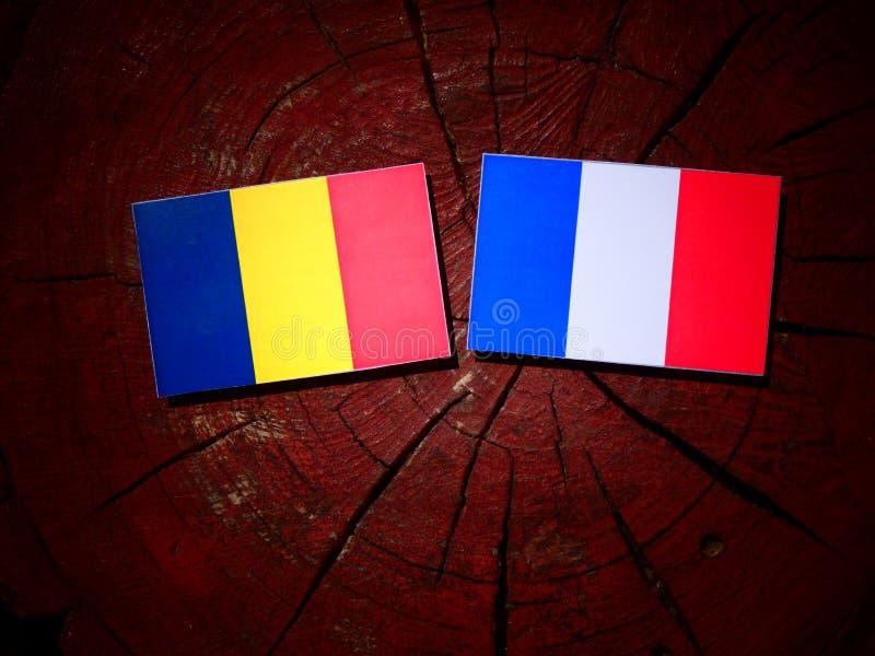 Drapeau du Tchad avec le drapeau français sur un tronçon d'arbre d'isolement image libre de droits