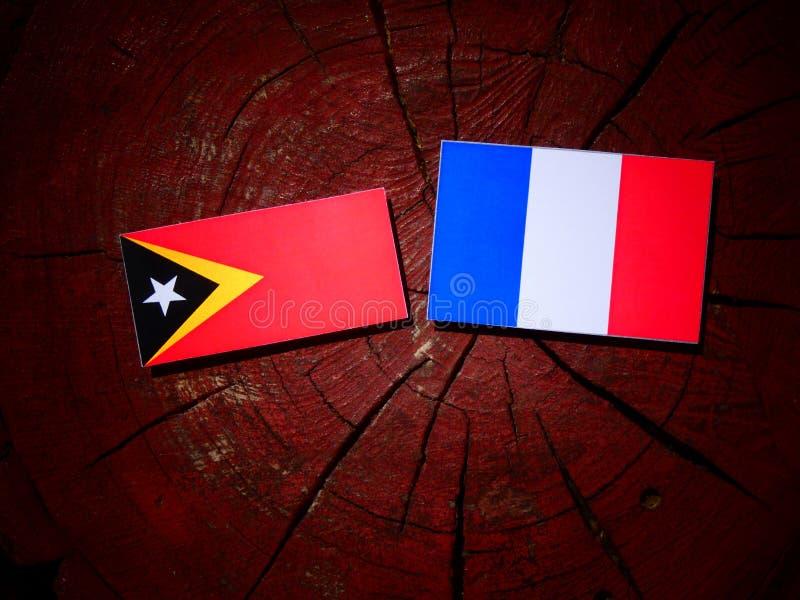 Drapeau du Timor oriental avec le drapeau français sur un tronçon d'arbre d'isolement photo stock