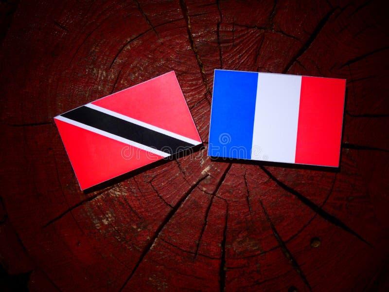 Drapeau du Trinidad-et-Tobago avec le drapeau français sur un isolat de tronçon d'arbre photo libre de droits