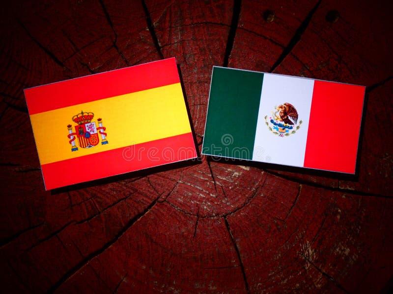 Drapeau espagnol avec le drapeau mexicain sur un tronçon d'arbre d'isolement image libre de droits