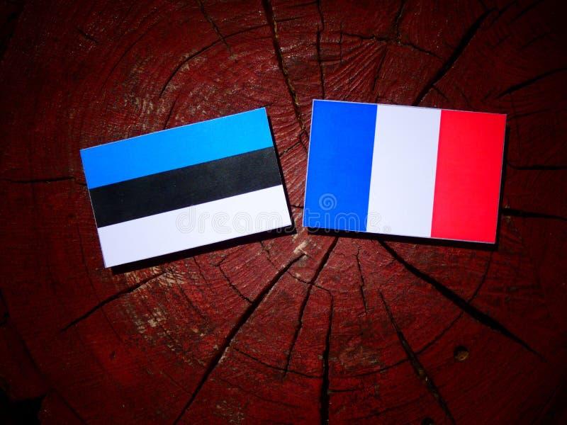 Drapeau estonien avec le drapeau français sur un tronçon d'arbre d'isolement images libres de droits