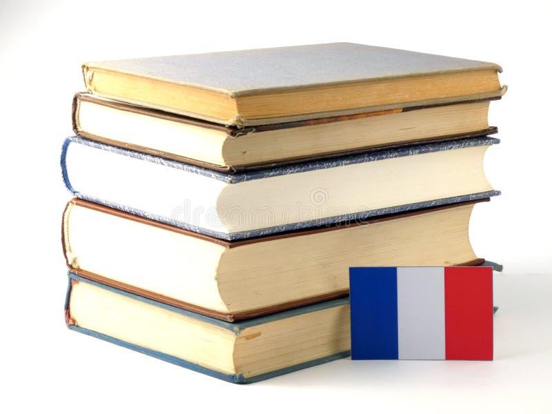 Drapeau français avec la pile des livres sur le fond blanc photographie stock libre de droits