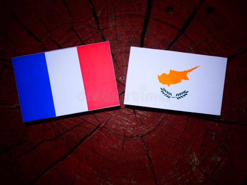 Drapeau français avec le drapeau chypriote sur un tronçon d'arbre d'isolement photographie stock libre de droits