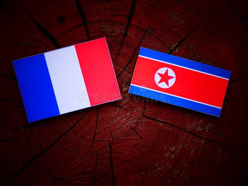 Drapeau français avec le drapeau coréen du nord sur un tronçon d'arbre photos stock