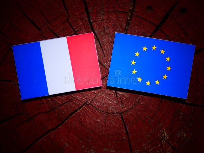 Drapeau français avec le drapeau d'UE sur un tronçon d'arbre d'isolement photos libres de droits