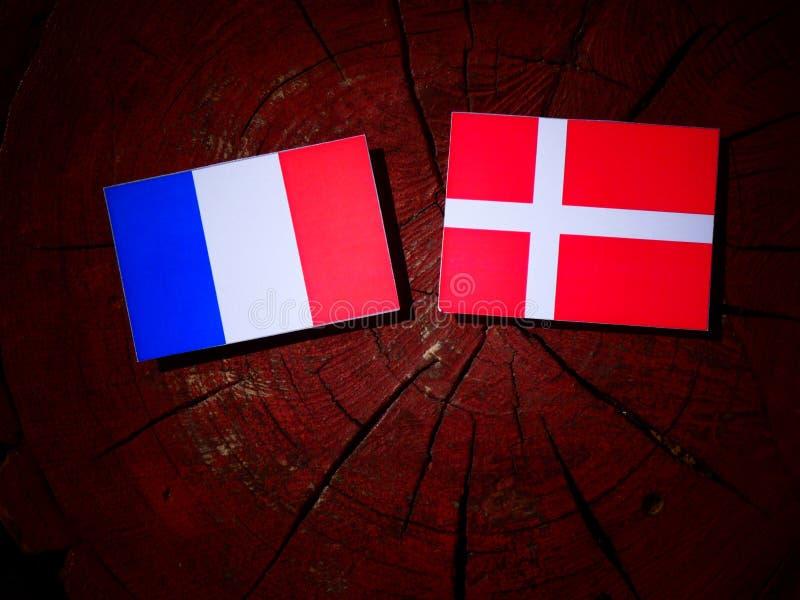 Drapeau français avec le drapeau danois sur un tronçon d'arbre d'isolement photographie stock