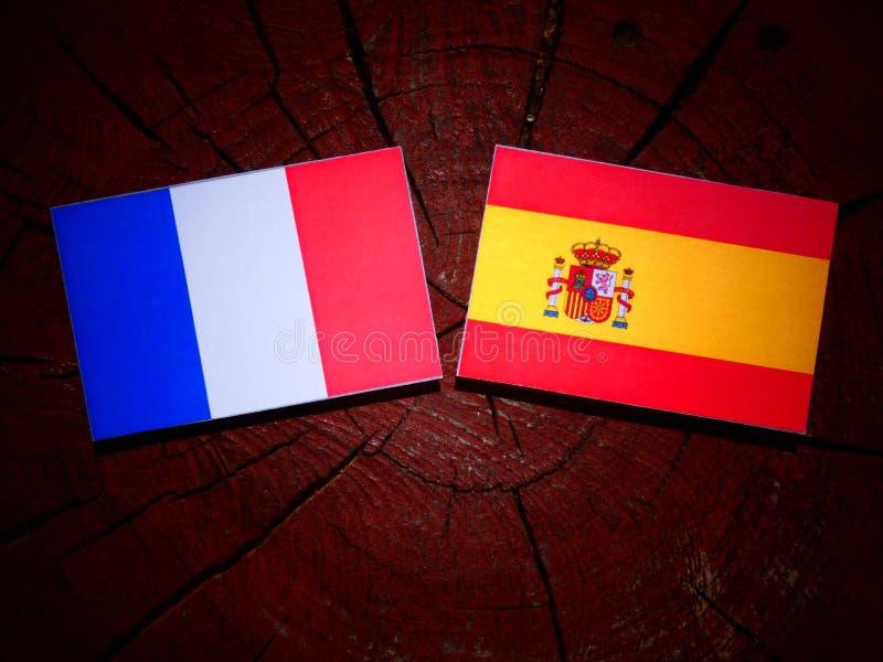 Drapeau français avec le drapeau espagnol sur un tronçon d'arbre photographie stock libre de droits