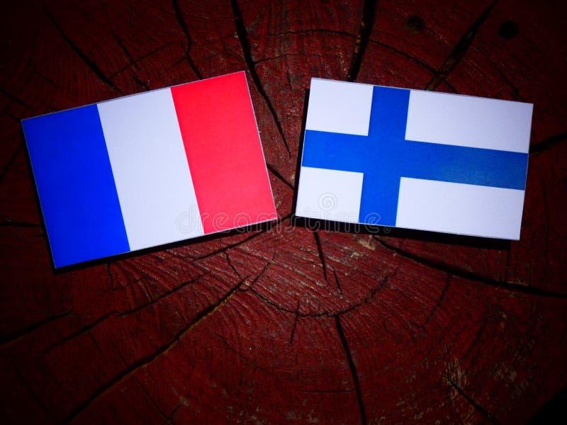 Drapeau français avec le drapeau finlandais sur un tronçon d'arbre d'isolement images stock