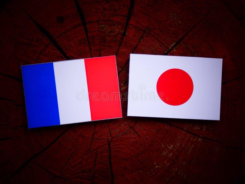 Drapeau français avec le drapeau japonais sur un tronçon d'arbre d'isolement image libre de droits