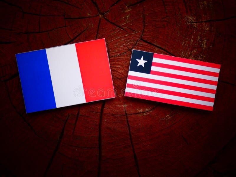 Drapeau français avec le drapeau libérien sur un tronçon d'arbre d'isolement photos libres de droits