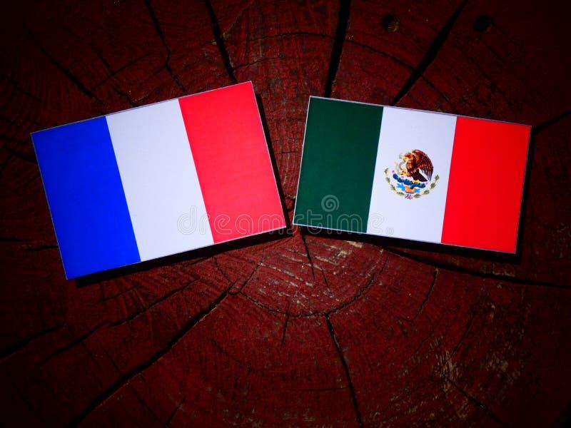 Drapeau français avec le drapeau mexicain sur un tronçon d'arbre d'isolement photos stock