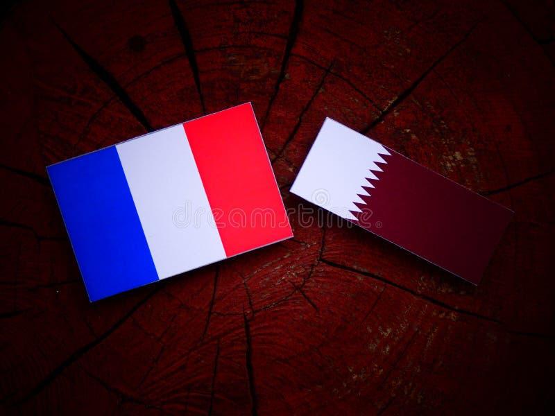 Drapeau français avec le drapeau qatari sur un tronçon d'arbre d'isolement images stock
