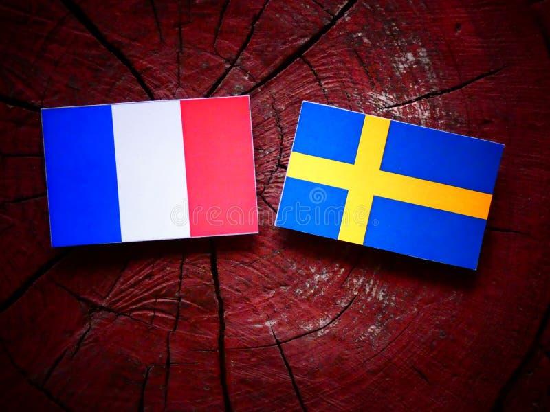 Drapeau français avec le drapeau suédois sur un tronçon d'arbre photographie stock libre de droits