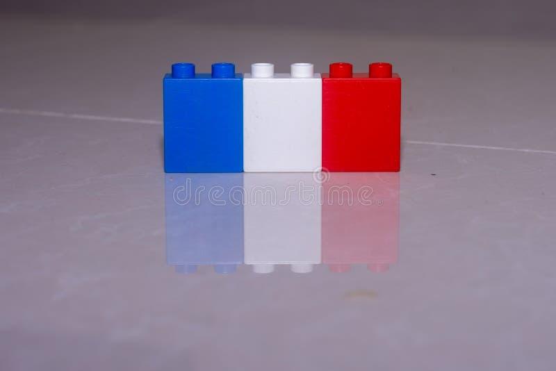 Drapeau français blanc, rouge et bleu fait de blocs de jouet sur une tuile avec une réflexion et un espace pour ajouter le concep images libres de droits