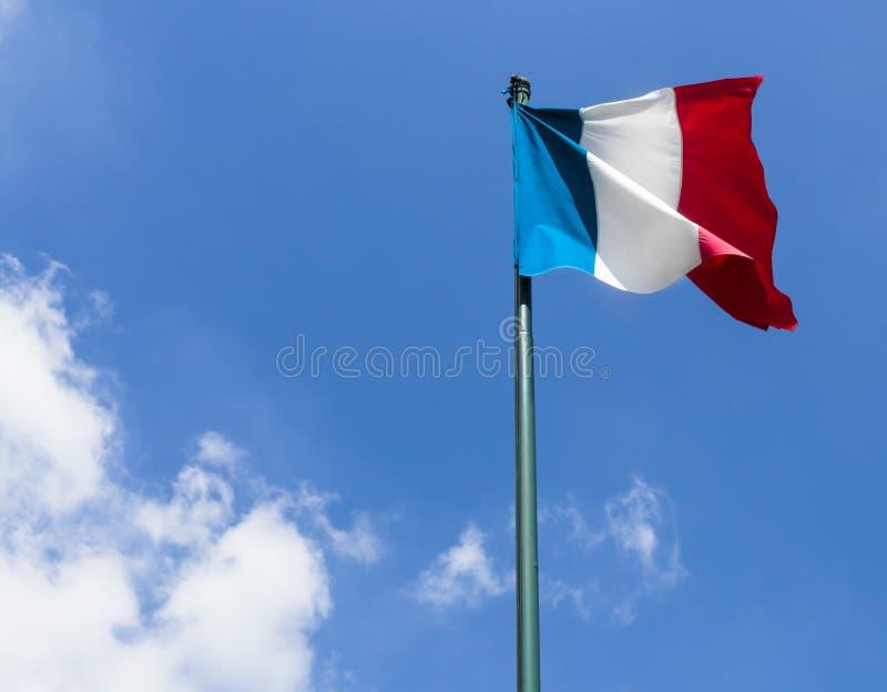 Drapeau français contre le ciel nuageux bleu photo stock