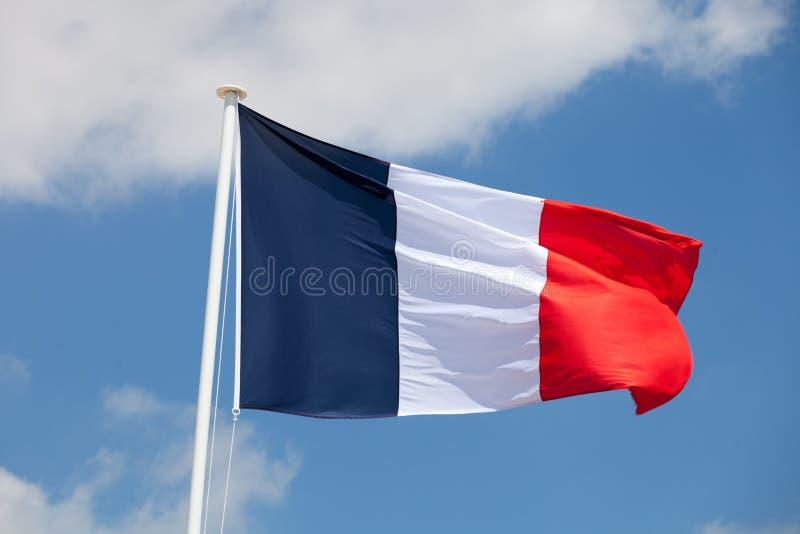 Drapeau français contre le ciel nuageux bleu photos stock