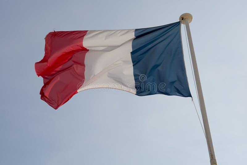 Drapeau français contre le ciel nuageux bleu image stock