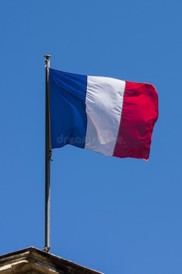 Drapeau français contre le ciel nuageux bleu images stock